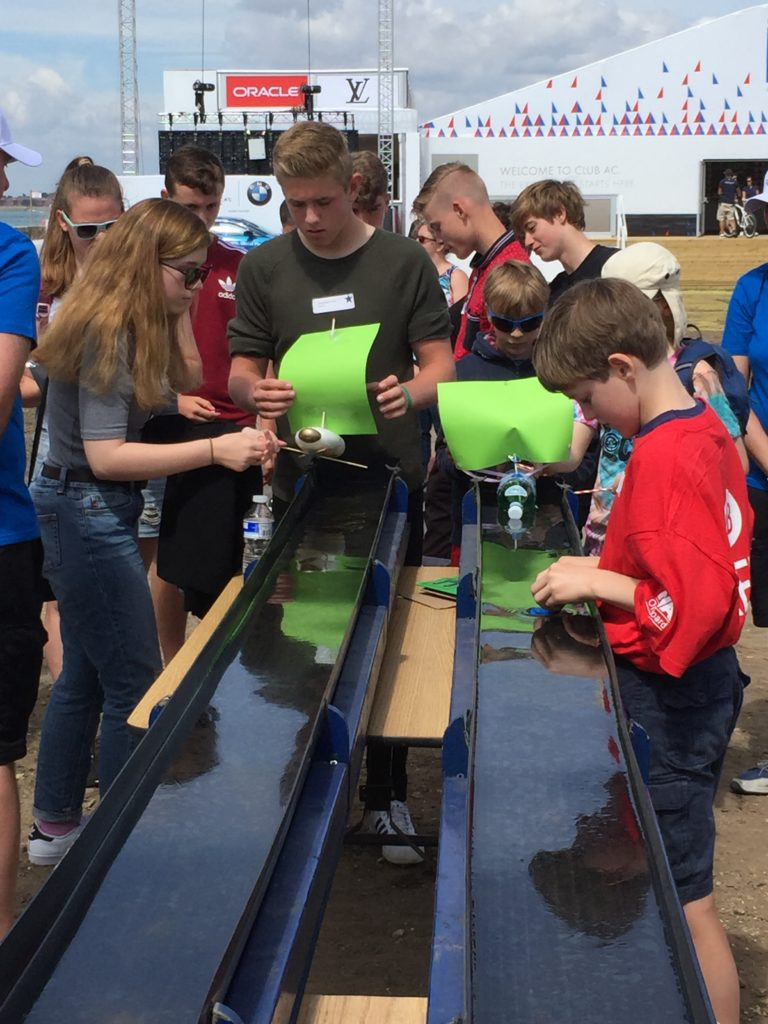 Young people race their boats they have created out of recyclable materials